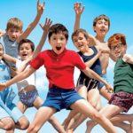 """Kadr z filmu """"Wakacje Mikołajka"""". Zdjęcie przedstawia grupę skaczących, radosnych dzieci"""