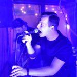 zdjęcie wokalisty zespołu taka karma śpiewającym do mikrofonu