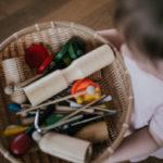 Zdjęcie przedstawiające dziecko trzymające kosz pełen instrumentów muzycznych